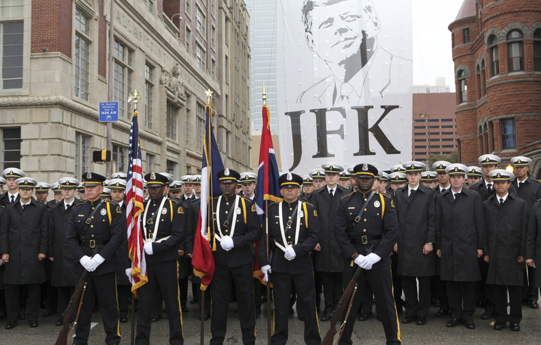 The Dallas Police Honorary Color Guard and the U.S. Naval Academy Men's Glee Club pose in front of a giant JFK banner at ceremonies commemorating the 50th anniversary of the death of President John F. Kennedy in Dealey Plaza in Dallas on Friday. Left: President Kennedy and first lady Jackie Kennedy.