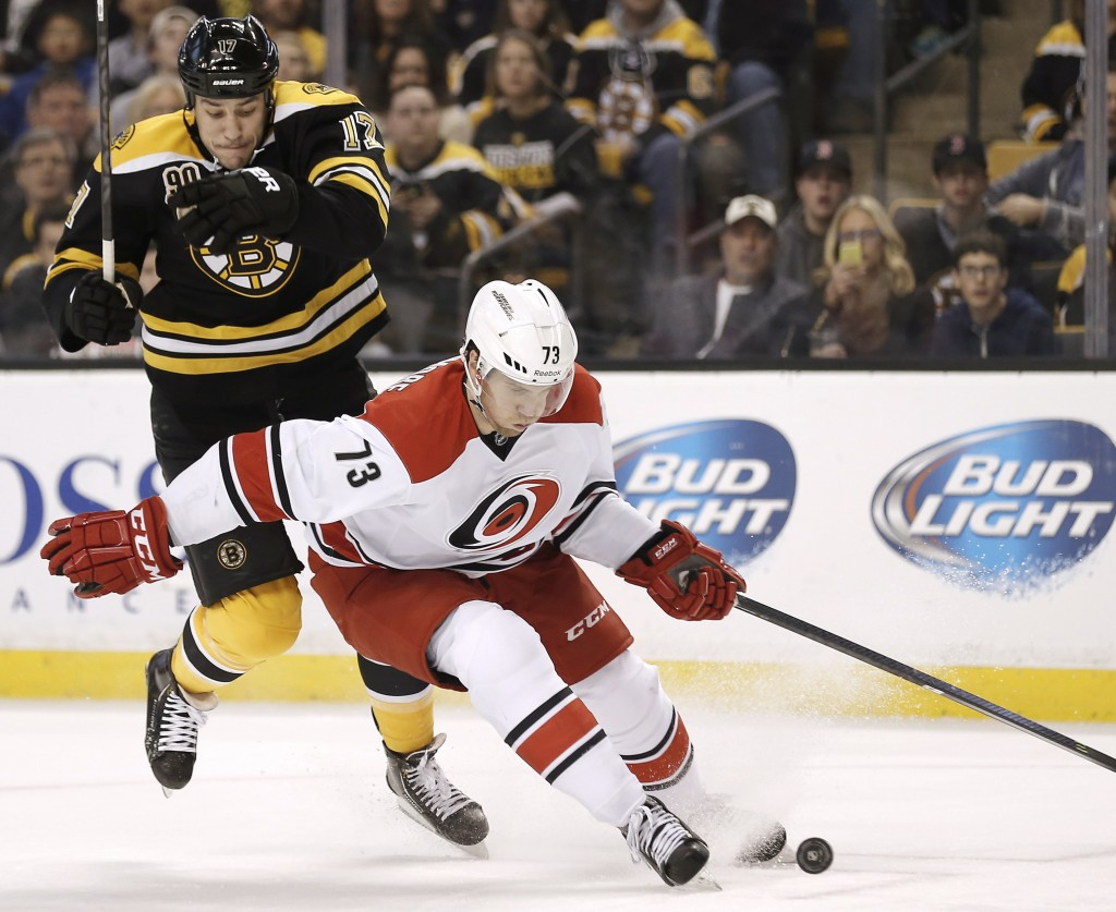 Carolina's Brett Bellemore gets a step ahead of a leaping Milan Lucic during Saturday afternoon's game in Boston, won by the Bruins on David Krejci's overtime goal.