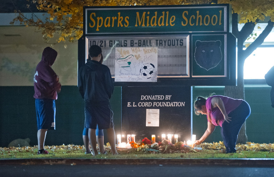 Community members pay their respects to Michael Landsberry, a 45-year-old eighth-grade math teacher, soccer coach and former Marine who was killed by a student at Sparks Middle School on Oct. 21 in Sparks, Nev.