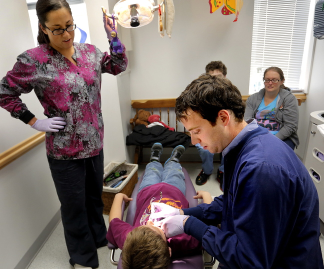 Dr. Michael Dowling works on patient Aiden Serber, 8, of Westbrook, as dental hygienist Trisha Drewry assists Wednesday at Falmouth Pediatric Dentistry. Dowling says new MaineCare audits carry excessive fines for small errors and the state has the ability to make the audits more fair.