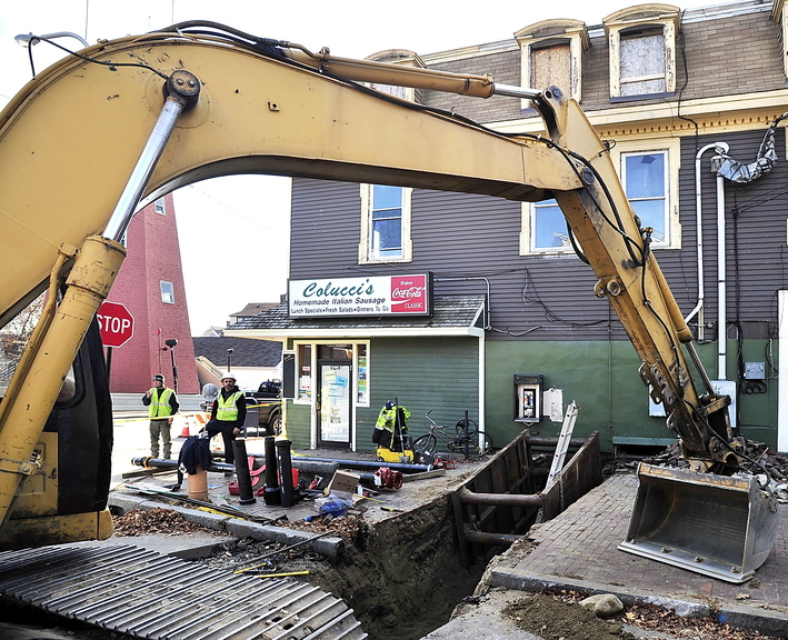 Framed by a large excavator, workers wait for a plumber to install the feed from the water main for sprinklers that will be installed throughout Colucci's Hilltop Superette at 135 Congress St. The building, damaged by an arson fire in March, has Colucci's on the ground floor and three upper-floor apartments.