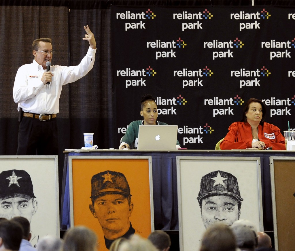 An auctioneer takes bids during a sale and auction of Houston Astrodome furnishings, Astroturf and staff uniforms Saturday. The world's first multipurpose domed stadium, once home to the Astros and the Oilers, has been closed to all events since 2009.