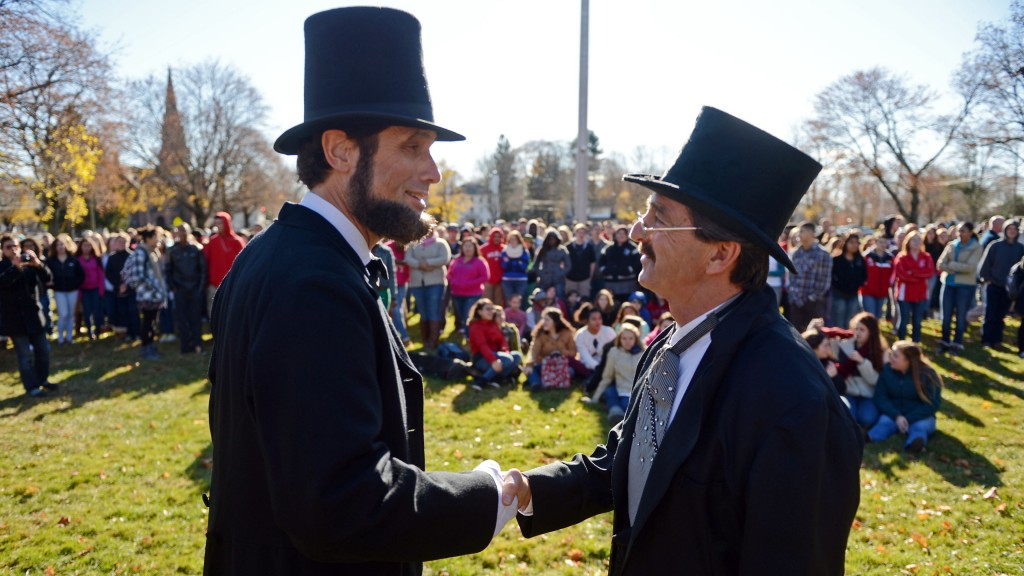 Abraham Lincoln re-enactor Howard Wright, left, is greeted by Norwich Free Academy Director of Student Affairs John Iovino on Chelsea Parade in Norwich, Conn., for an event to mark the 150th anniversary of the Gettysburg Address Tuesday, Nov. 19, 2013. Wright was introduced by Iovino and delivered prefacing remarks about Gettysburg and Lincoln's words before reciting the actual speech.