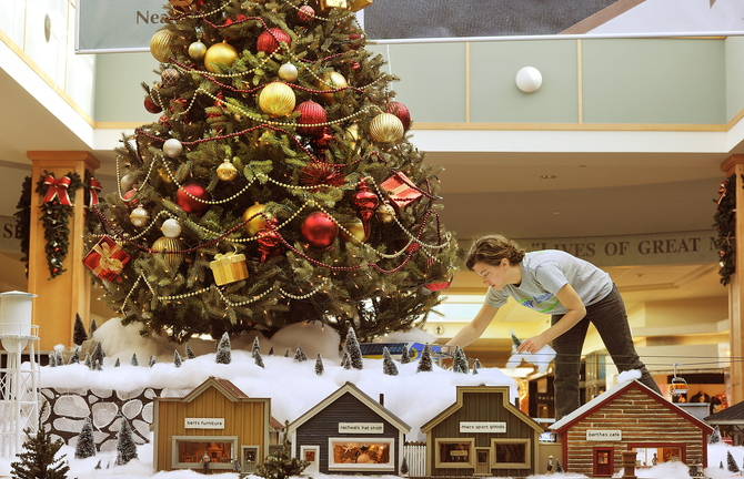 Maine Mall marketing manager Stephanie Millette puts some finishing touches on the holiday model train display in the center of the mall in South Portland on Tuesday.