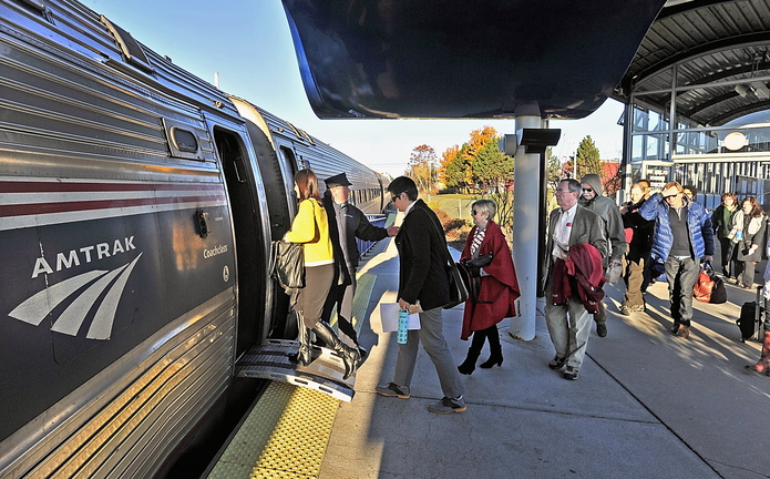 Conductor Brian Labreck greets passengers heading to Boston and stops in between as they board the Downeaster in Portland on Wednesday morning. Two of the five daily Portland-Boston trips extend to Brunswick.