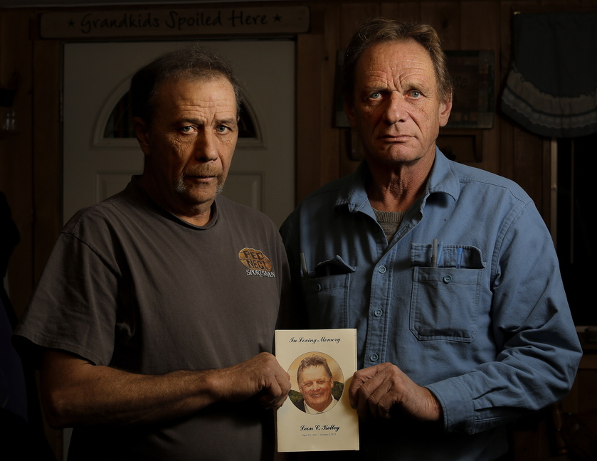 "Brothers Joseph and William Kelley hold a picture of their deceased brother, Leon, while standing in the kitchen of Joseph's Woolwich home Wednesday. Leon Kelley was shot dead at a North Yarmouth bee farm last month, and Merrill ""Mike"" Kimball, 70, of Yarmouth was indicted on murder charges."