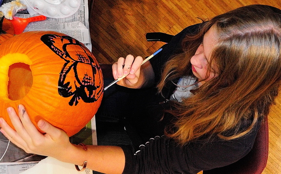 Kyara Dawbin paints a pumpkin during the after-school art program hosted by students from the University of Maine at Augusta on Wednesday at Johnson Hall in Gardiner. Students in the program say they enjoy the creative freedom and art supplies that are offered.