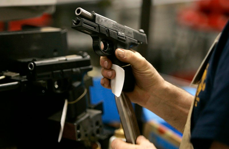 In this 2006 file photo, an employee loads a magazine into the grip of a model 9VE pistol while test firing at the Smith & Wesson factory in Springfield, Mass. Smith & Wesson says it will eliminate 37 jobs from its Houlton, Maine plant as it shifts the location's focus to polymer-frame handguns and moves some manufacturing to its Springfield location.
