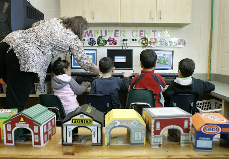 In this March 2007 file photo, teacher Ellen Vicens, left, helps pre-kindergarten students with computers at Carlin Springs Elementary School in Arlington, Va. Maine lawmakers were urged Monday to support a bill that would make Maine one of a handful of states to offer pre-kindergarten in every school district.