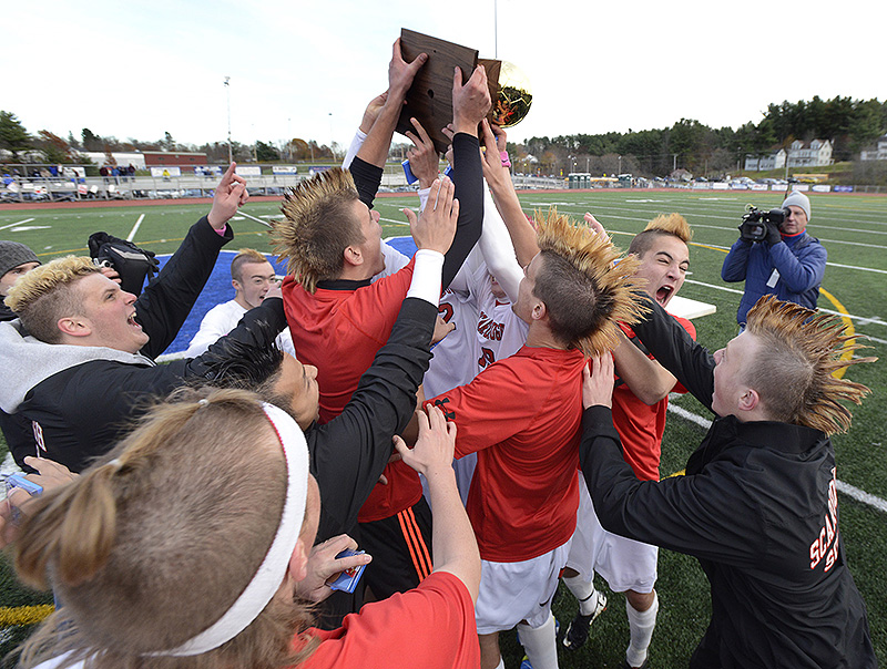 Members of the Scarborough boys' soccer team hoist the trophy captured after a 2-1 win over Hampden Academy in the Class A state championship game on Saturday at McMann Field in Bath. BoysAsoccer