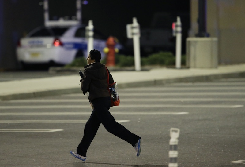 A woman runs in the parking lot of the Garden State Plaza Mall following reports of a shooter Mondayin Paramus, N.J. Hundreds of law enforcement officers converged on the mall Monday night after witnesses said multiple shots were fired there.