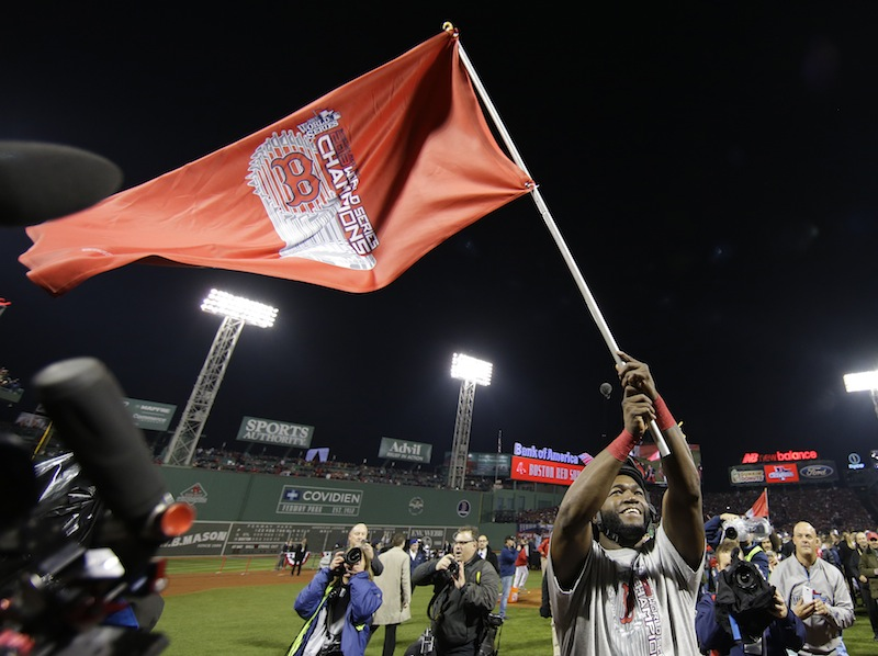 Boston Red Sox's David Ortiz waves a flag after Boston defeated the St. Louis Cardinals in Game 6 of baseball's World Series Wednesday, Oct. 30, 2013, in Boston. The Red Sox won 6-1 to win the series. MLB