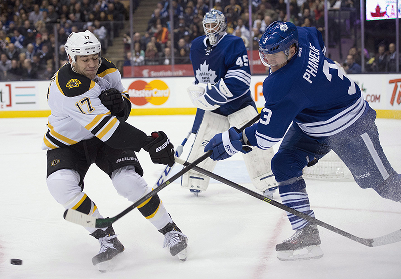 Toronto Maple Leafs defenseman Dion Phaneuf (3) clears the puck past Boston Bruins left winger Milan Lucic (17) as goaltender Jonathan Bernier looks on during first period NHL action in Toronto on Sunday Dec. 8, 2013. (AP Photo/The Canadian Press, Frank Gunn) Canada;hockey;NHL;athlete;athletes;athletic;athletics;Canadian;c