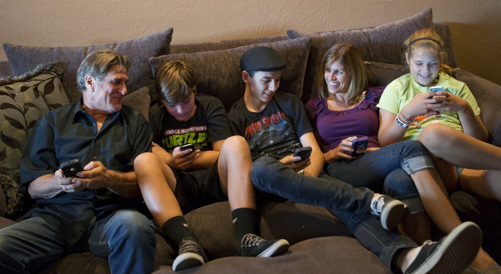 "The Moore family, from left, Bill, Dylan, 13, Randy, 18, Sandra and Alyssa, 12, talk about how they use their smartphones, tablets and computers at their home in San Jose, Calif. ""We spend a lot of time convincing Bill that it's easier this way,"" said his wife."