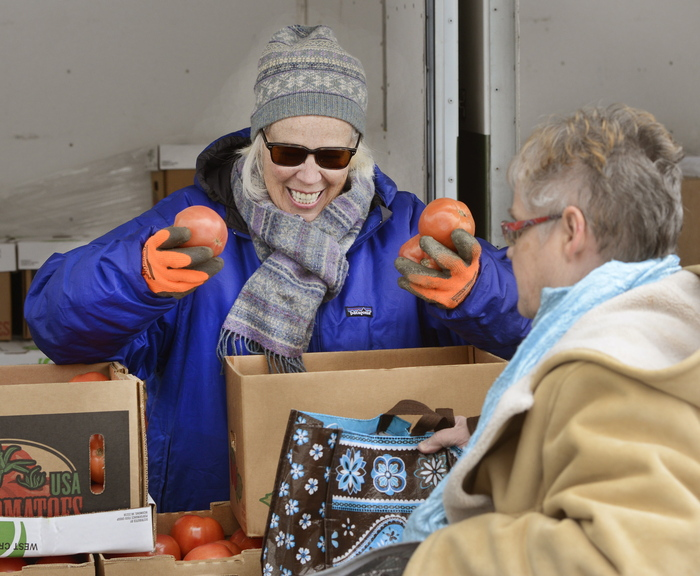 Volunteer Sheila O'Grady hands out tomatoes.