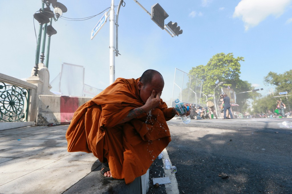 A Thai Buddhist monk washes his eyes after riot police fired tear gas at anti-government protesters in Bangkok on Sunday, the seventh day of demonstrations.