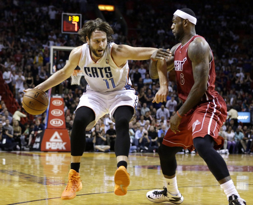 Charlotte's Josh McRoberts drives to the basket as Miami's LeBron James defends during second-half action in Sunday's game at Miami, a 99-98 win for the Heat.