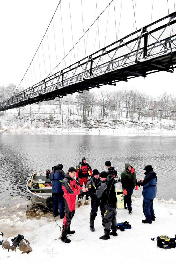 Divers with the Maine State Police and Maine Department of Marine Resources prepare to enter the Kennebec River under the Two-Cent Bridge in Waterville on Monday.