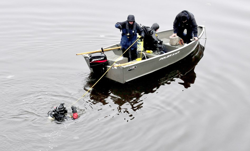 A diver is tethered to a boat Monday during a search for evidence related to the killing of Thomas Namer in Vassalboro.