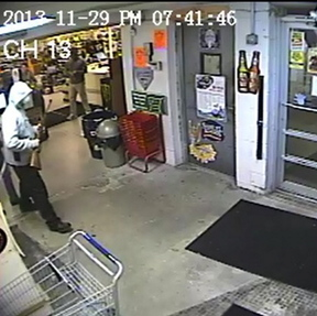Police are seeking information on a man, seen on Friday in this security camera image, who carried a rifle into RSVP Discount Beverage on Forest Avenue in Portland.