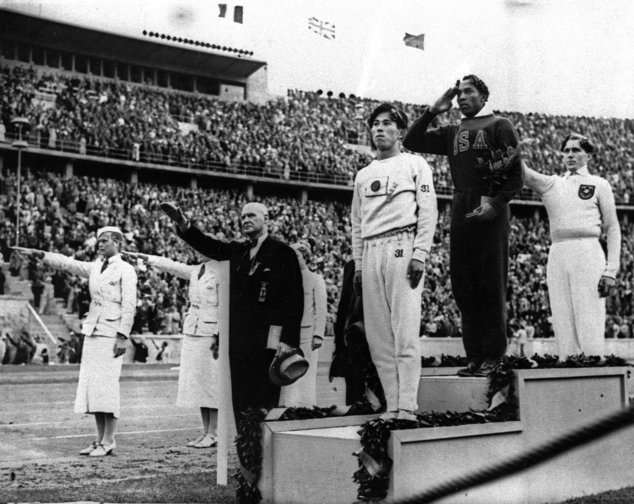 In this 1936 file photo, Olympic broad jump medalists salute during the medals ceremony at the Summer Olympics in Berlin. From left on the podium are: bronze medalist Jajima of Japan, gold medalist Jesse Owens of the United States and silver medalist Lutz Long of Germany.