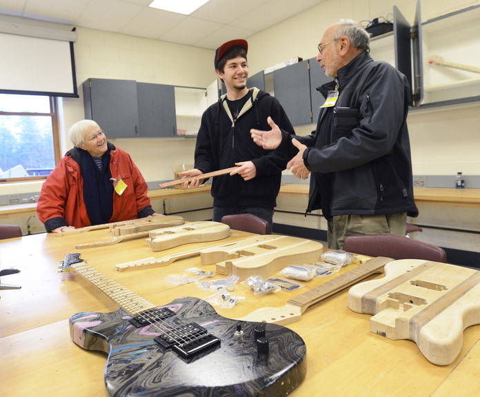 Noble High School senior Mike Lavigne shows Sandy and Dave Perloff some guitars in different stages of completion. The Perloffs provided grants to fund the class at the North Berwick school and hundreds of other Maine projects, and make it a point to revisit schools twice a year to check on the programs' progress.