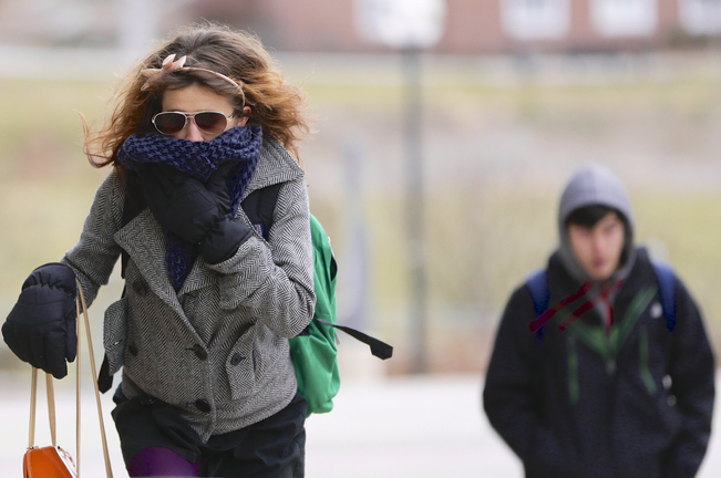 A student on the campus of the University of Nebraska-Omaha, in Omaha, Neb., tries to block out the cold Thursday as temperatures registered 13 degrees with a wind chill of minus 1.