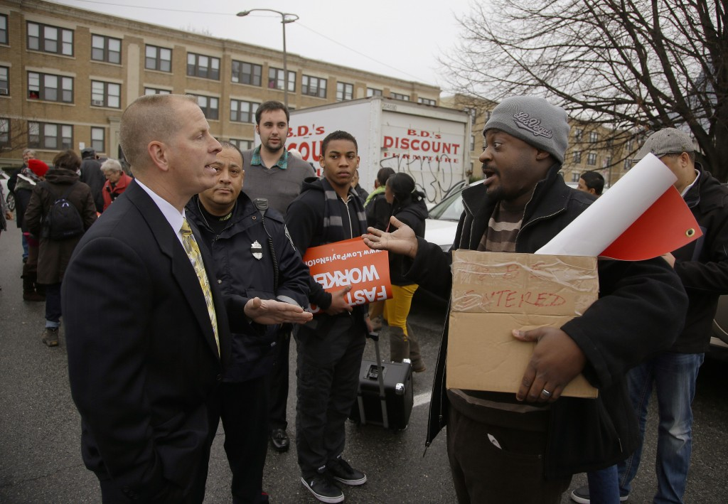 A man refusing to identify himself, left, confronts protest organizer Marlon Washington, right, before his group takes part in a nationwide protest supporting higher wages for workers in the fast-food industry and other minimum wage jobs at a Burger King restaurant in Boston on Thursday, Dec. 5, 2013 The unidentified man told Washington that his group had no right to be on the restaurant's premises and threatened the towing of cars. No cars were towed.