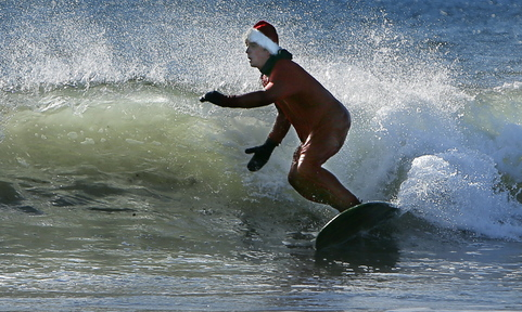 Dressed in a Santa Claus suit, Ryan McDermott of Freeport surfs at Gooch's Beach in Kennebunk on Saturday.