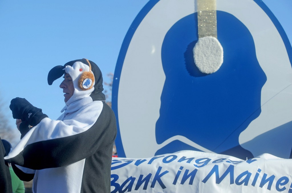 Peter Judkins, president of Franklin Savings Bank, takes a picture while dressed like a penguin at the annual Chester Greenwood Day parade in downtown Farmington on Saturday.