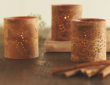 Cinnamon-bark tea lights with perforations in the bark let out the glow of candlelight.