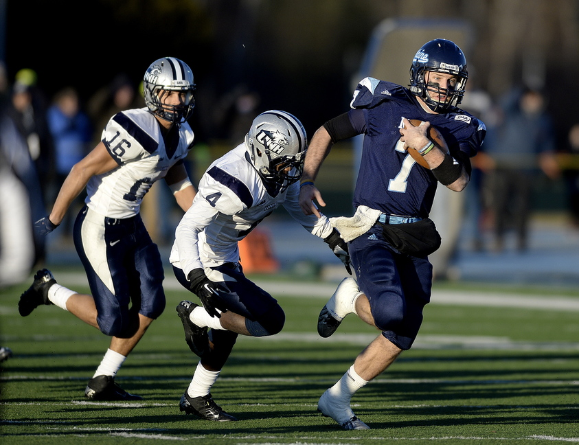 Maine quarterback Marcus Wasilewski eludes UNH defenders Nick Cefalo (16) and Manny Asam (4) as he runs for a first down during the second quarter of a second round playoff football game between UMaine and UNH at Alfond Stadium in Orono on Saturday.