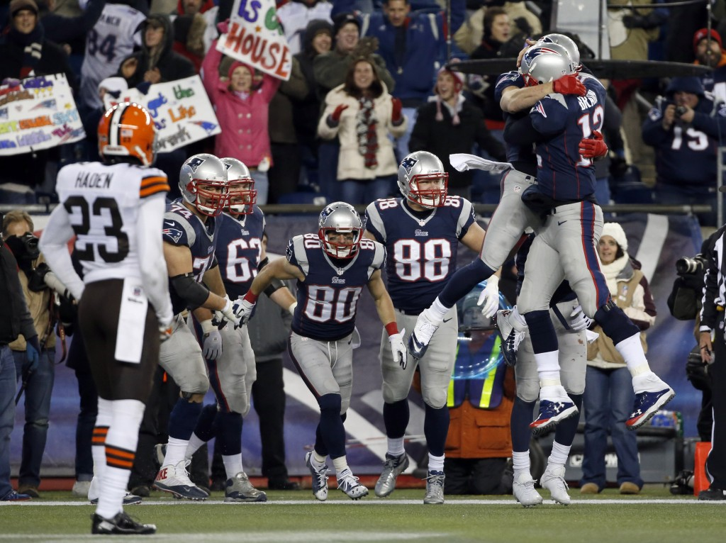 New England Patriots quarterback Tom Brady (12) celebrates his go-ahead touchdown pass to wide receiver Danny Amendola (80) with Julian Edelman, hugging Brady, in the fourth quarter of an NFL football game against the Cleveland Browns, Sunday, Dec. 8, 2013, in Foxborough, Mass. The Patriots came from behind to win 27-26.