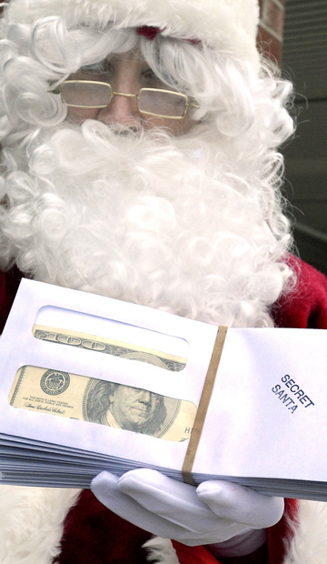 The Secret Santa displays a handful of envelopes containing $100 bills Friday. Since 2009, the generous businessman has given away $80,000 to brighten the Christmas season.