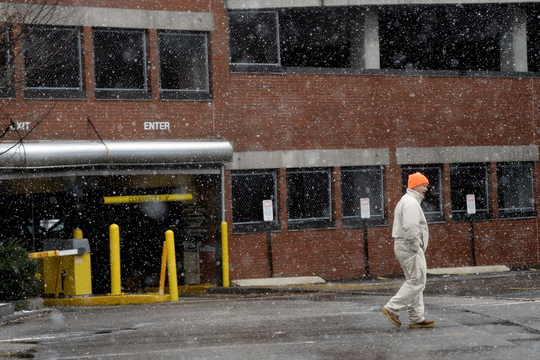 A pedestrian walks through light snow near the One City Center Parking Garage in Portland Monday. Walking became treacherous later.