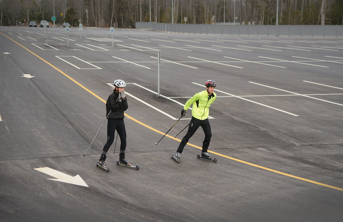 Ski team members Sam Alexander, right, a Yarmouth High School senior, and Emma Torres, a junior, roller-ski Sunday at the park-and-ride lot off Exit 15. They said the fresh asphalt, flat terrain and lack of obstacles make the lot a perfect place to roller-ski.