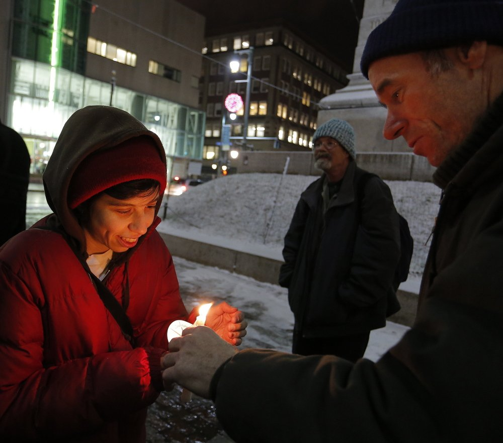 Liz Kramer of Portland has her candle lit by Ken Kohl, also of Portland, during a vigil in Monument Square on Tuesday in memory of the late South African President Nelson Mandela.