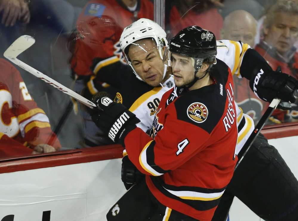 Boston's Jarome Iginla, left, tries to get past the Flames' Kris Russell during the second period of the Bruins' 2-1 win at Calgary. The Flames honored Iginla before the game – his first in Calgary as an opponent.