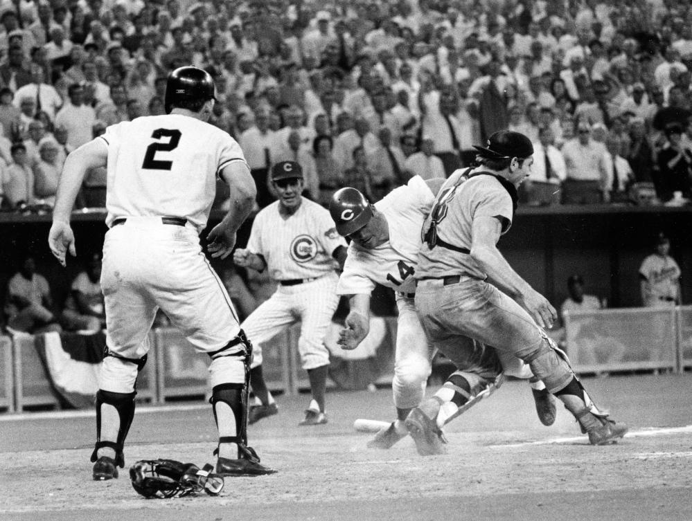 In this July 14, 1970 file photo, Cincinnati Reds' Pete Rose (14) slams into Cleveland Indians' catcher Ray Fosse to score a controversial game-winning run for the National League team in the 12th inning of the 1970 All-Star game in Cincinnati. Fosse suffered a fractured shoulder in the collision. Looking on are the Reds' third base coach Leo Durocher, and Cincinnati Reds' next hitter Dick Dietz (2). Major League Baseball plans to eliminate home plate collisions, possibly as soon as next season but no later than by 2015. New York Mets general manager Sandy Alderson, chairman of the rules committee, made the announcement Wednesday, Dec. 11, 2013 at the winter meetings. Player safety and concern over concussions were major factors in the decision.