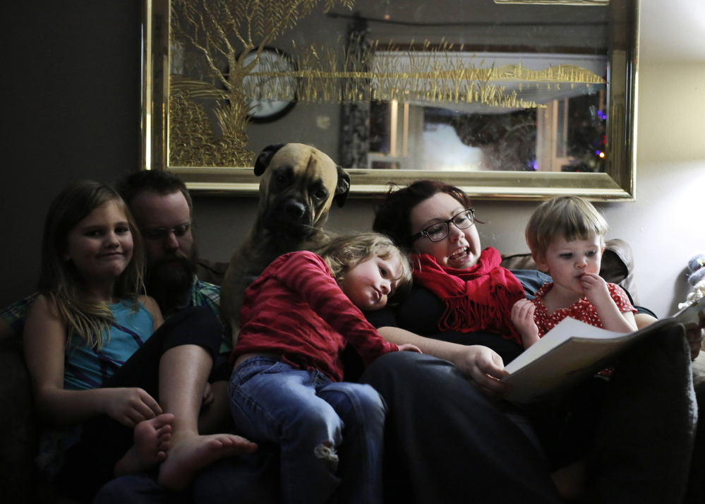 Carli Hopkins, 4, rests her head on mother Rebecca Hopkins, who is telling a story as Carli's sister Violet, father Jason Hopkins, bull-mastiff Coco and younger sister River listen. Carli was on the losing end of the sequestration list.