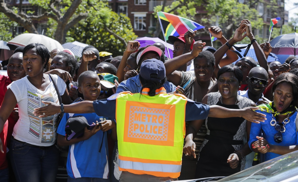 A police officer blocks people after access to see former South Africa President Nelson Mandela was closed on the final day of his casket lying in state Friday.