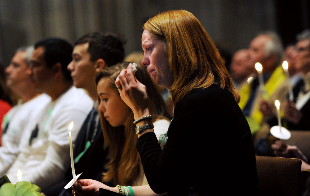 Miranda Pacchiana, center, of Newtown, Conn., wipes her eye during a National Vigil for Victims of Gun Violence at Washington National Cathedral in Washington on Thursday, two days before the first anniversary of the Sandy Hook Elementary School mass shooting. Federal gun laws remained unchanged after the furor died down, leaving states to act.