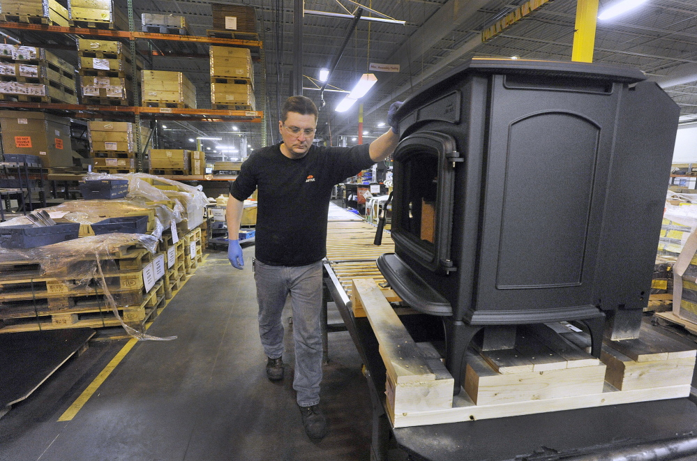 Jotul Stove employee Joe Osmond, who works at the Jotul North America plant in Gorham moves a finished stove down a conveyor line for final inspection and packaging.