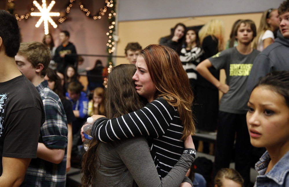 Freshman Allie Zadrow, center right, hugs classmate Liz Reinhardt at a church after a shooting at nearby Arapahoe High School in Centennial, Colo., on Friday, Dec. 13, 2013. Students from the school were evacuated to the church. Arapahoe County Sheriff Grayson Robinson said the shooter shot two others at the school, before apparently killing himself.