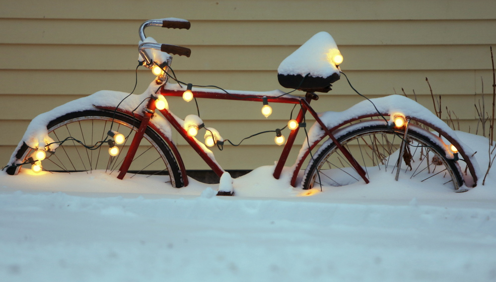 A bicycle decorated for the holidays at a home on Brown Street in Kennebunk is half-buried in snow from Sunday's storm.