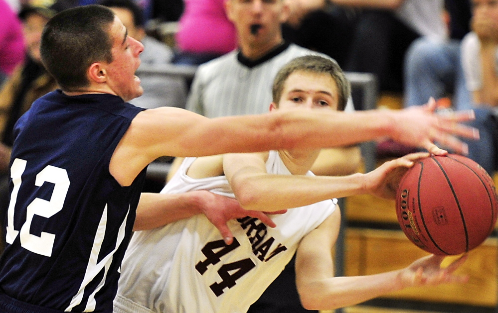 Billy Ruby of Gorham slips a pass under tough defense applied by Justin Zukowski of Portland during their SMAA game Tuesday night. Zukowski scored 15 points and the Bulldogs remained unbeaten through four games with a 60-40 victory.