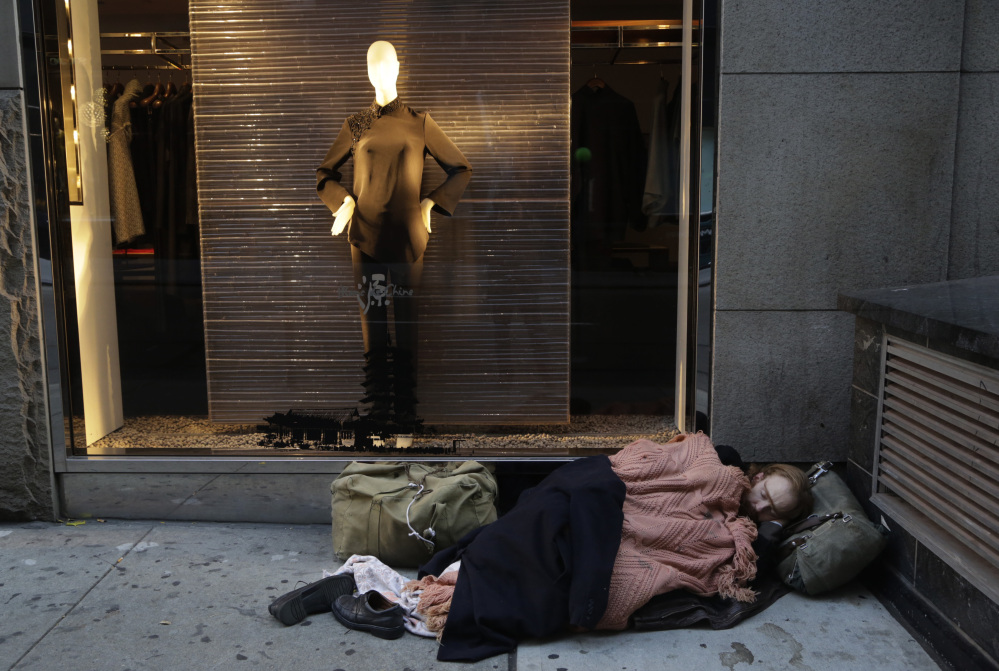 A destitute man sleeps on the sidewalk under a holiday window at Blanc de Chine in New York in November. The growing gap between the richest Americans and everyone else is hurting the U.S. economy, say a majority of more than three dozen economists surveyed this month by The Associated Press.