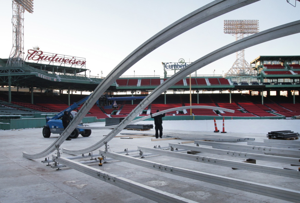 "A crew sets up the ""Monster Sled,"" created by StackBox Structures LLC of Portland, on Tuesday at Fenway Park."