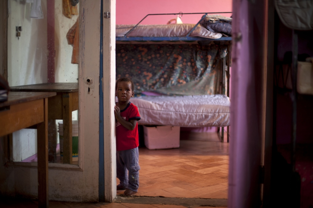 A young boy stands in his room in the U.S.-based Church of Bible Understanding orphanage in Kenscoff, Haiti.