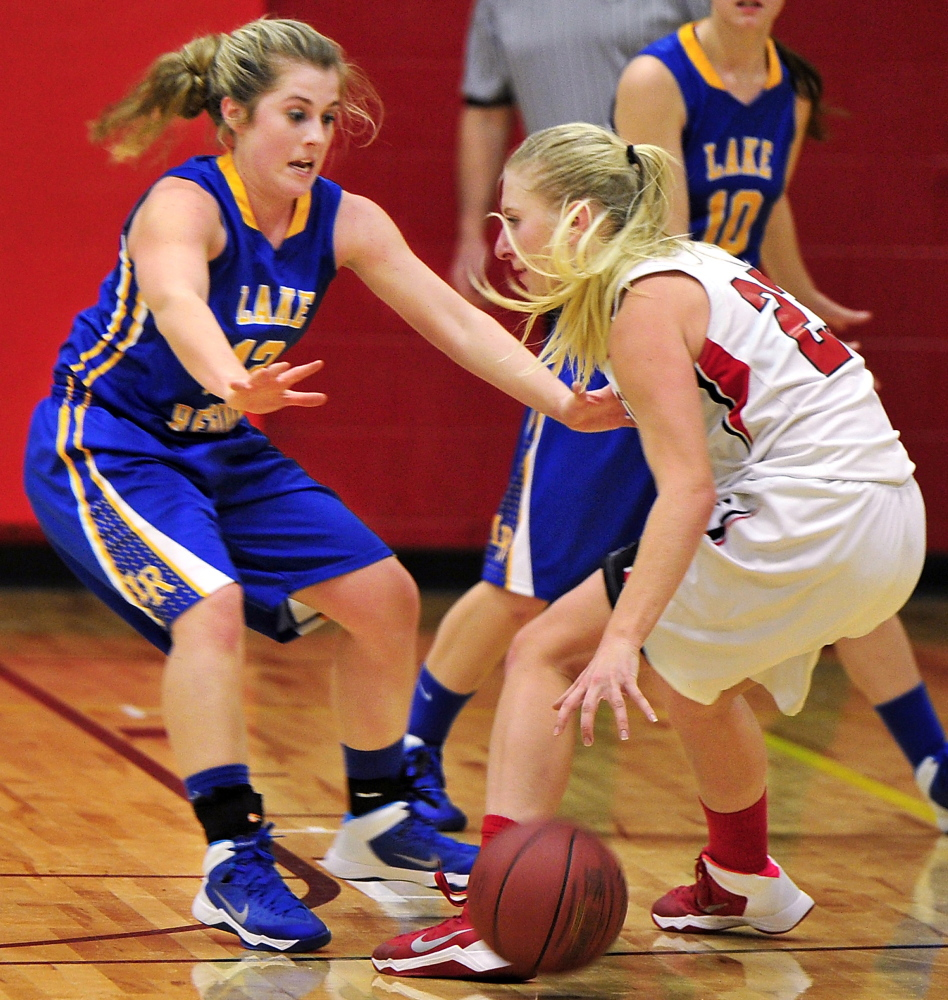 Sarah Hancock of Lake Region left, attempts to hold her ground while defending against Alison Furness of Wells.